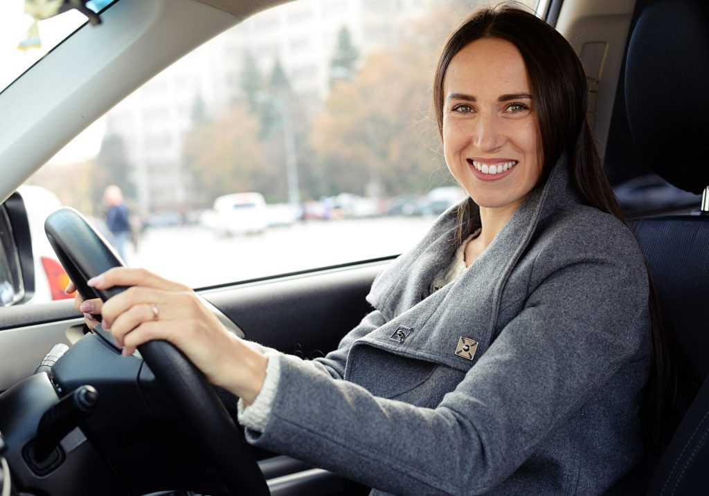 Woman smiling while behind the wheel of a car