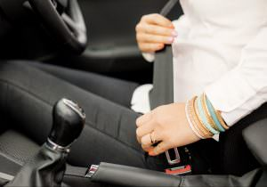 Woman putting on seatbelt