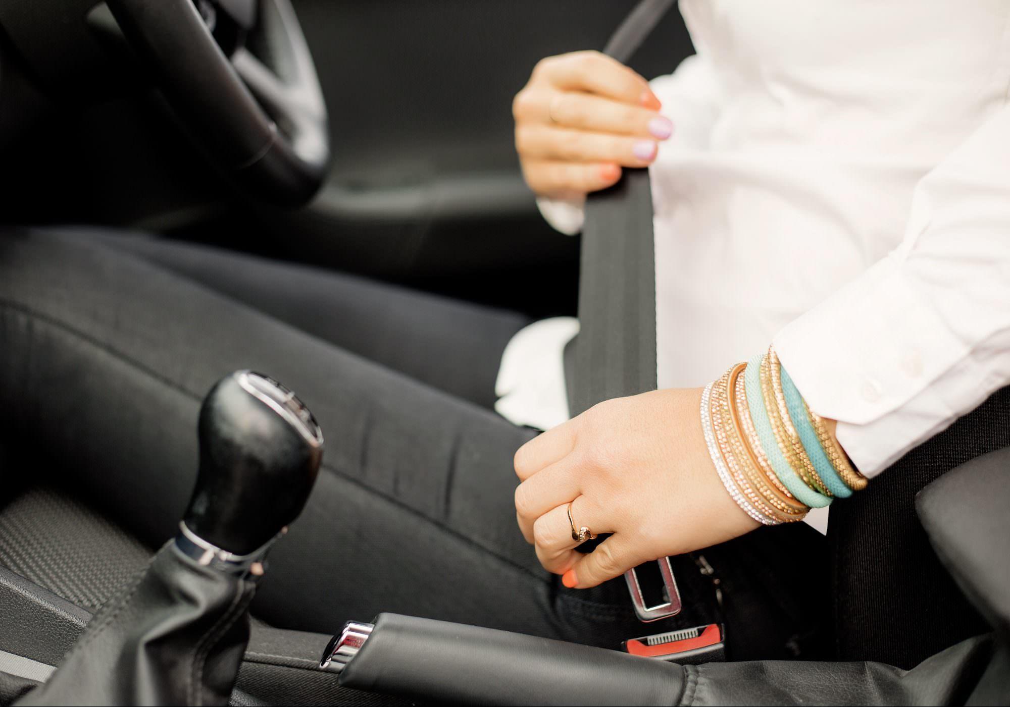 Woman putting on seatbelt