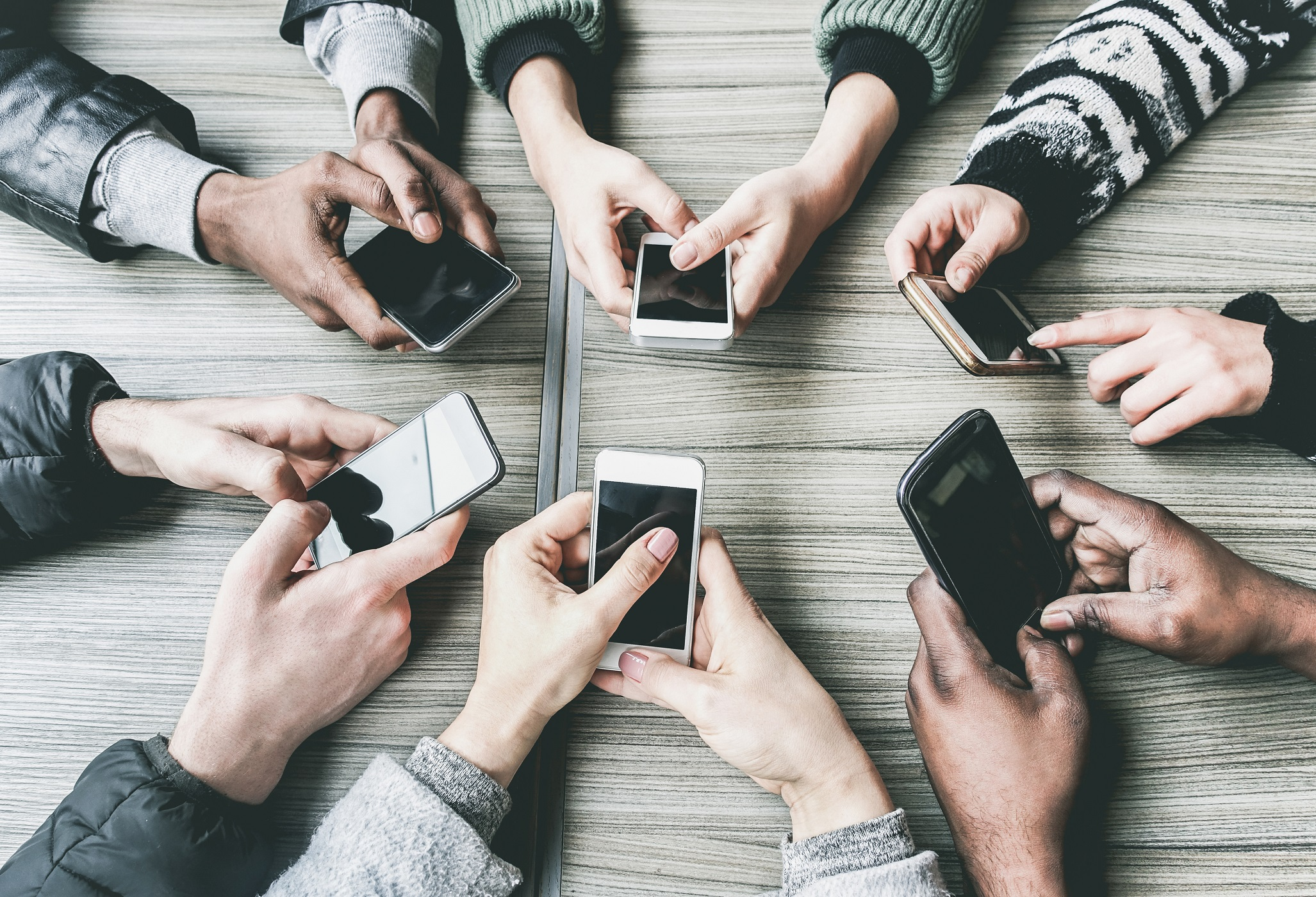 Group of friends having fun together with smartphones