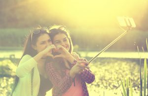 Two pretty teenage girls making heart shape with hands and taking selfie on mobile phone with stick in the nature beside river. Positive emotions
