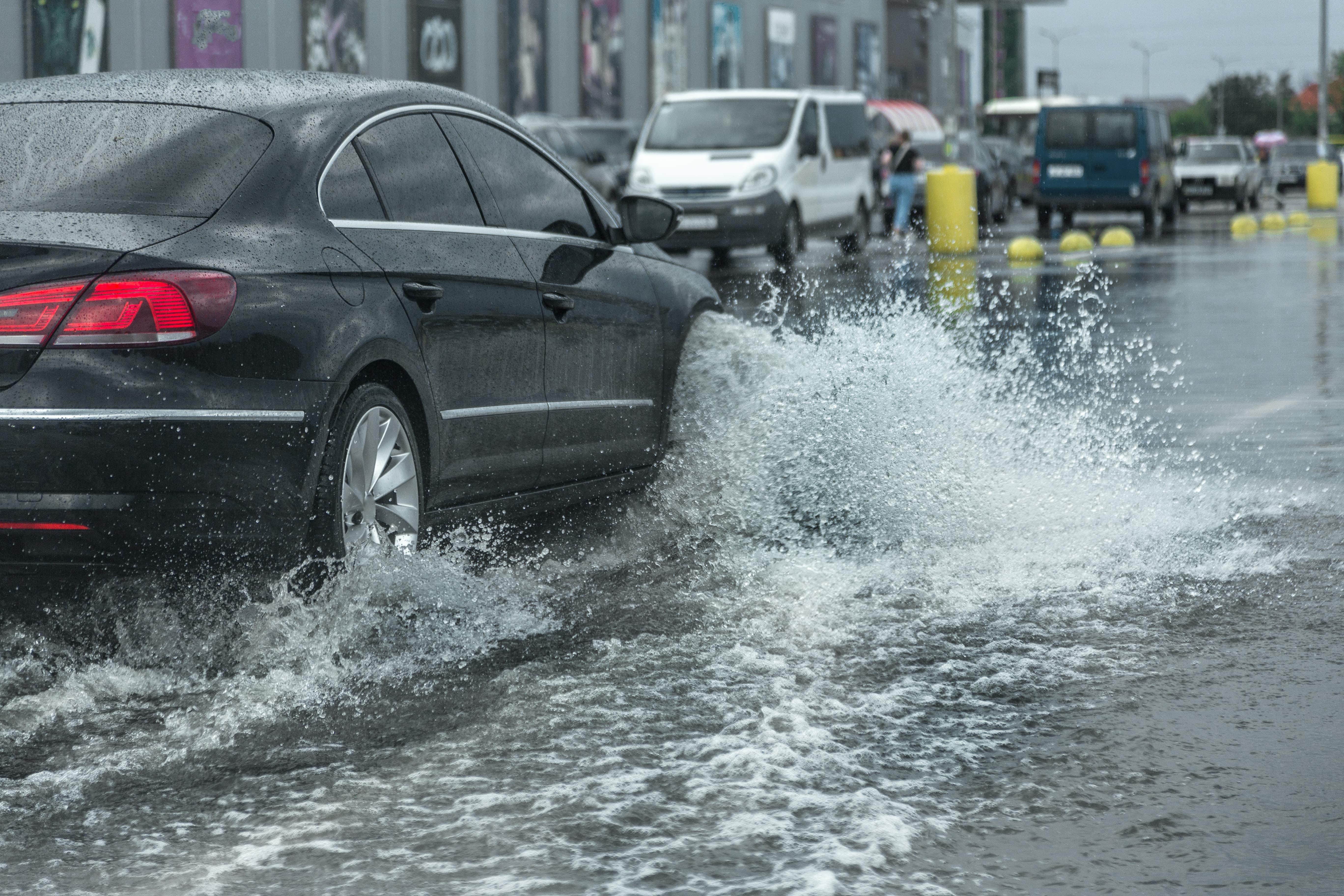 Black car driving through large puddle