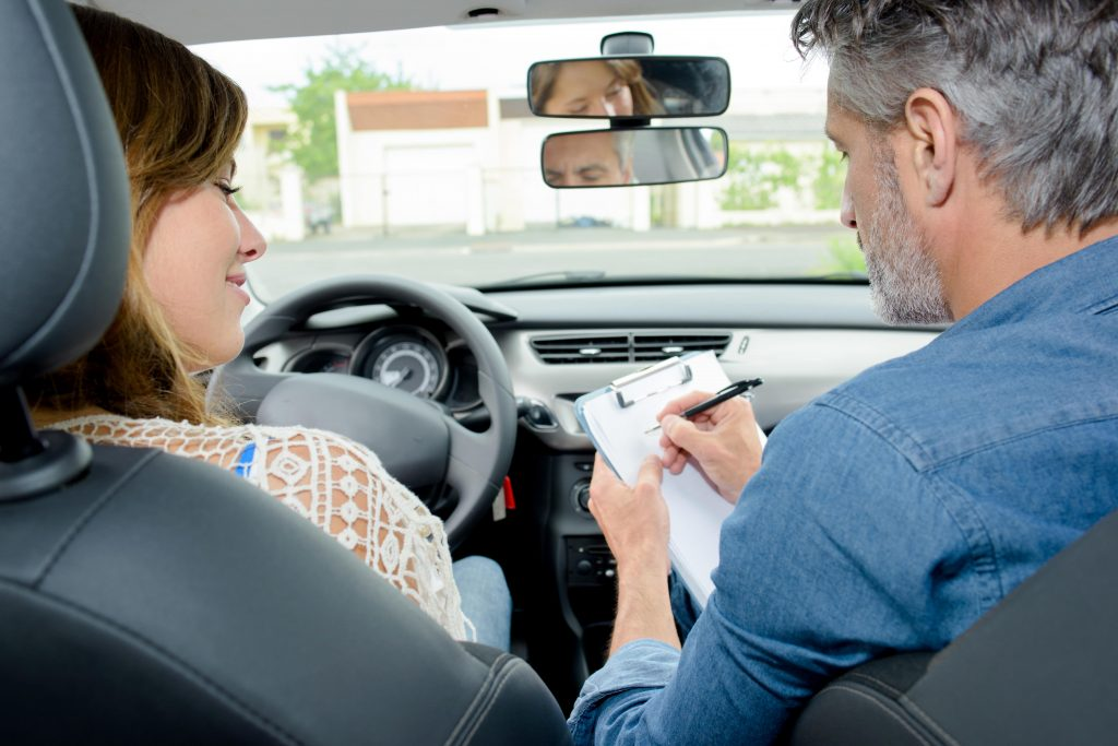 Driving examiner marking paper with student