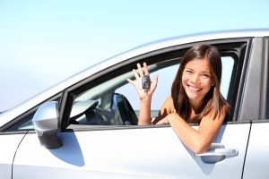 Driver leaning out of window with keys to new car