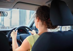 Female driver with both hands on steering wheel